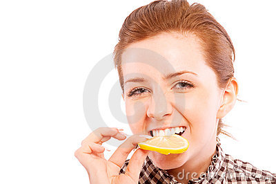 Young woman eating sour lemon, making grimace