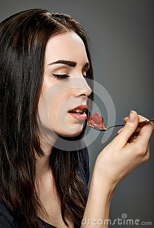 Young attractive woman eating strawberry cake.