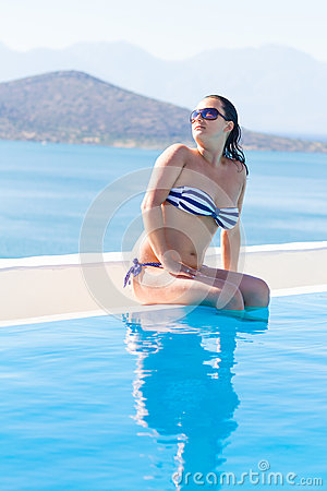 Young woman on the edge of swimming pool