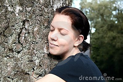 Young woman embrace big tree