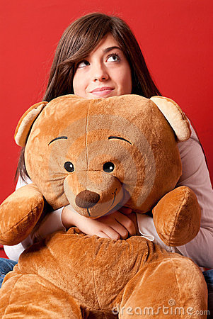 Young woman embracing teddy bear looking up