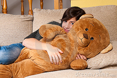 Young woman embracing teddy bear lying on on sofa