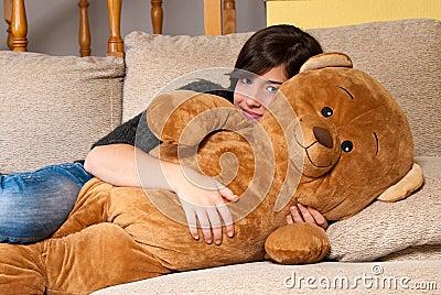 Young woman embracing teddy bear lying on on sofa