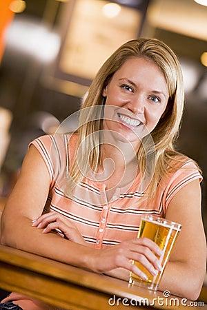 Young woman enjoying a beer at a bar