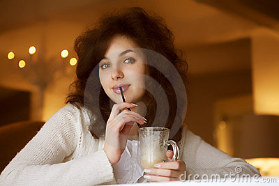 Young woman enjoying latte coffee in cafe