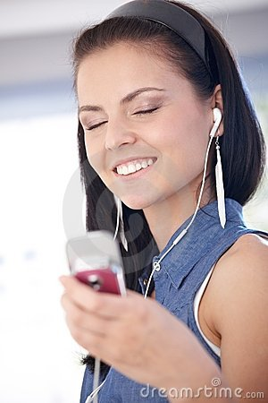 Young woman enjoying music smiling