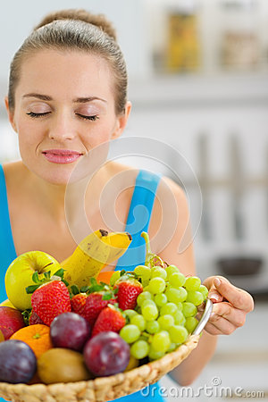 Young woman enjoying plate of fresh fruits