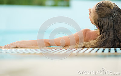 Young woman enjoying pool . rear view