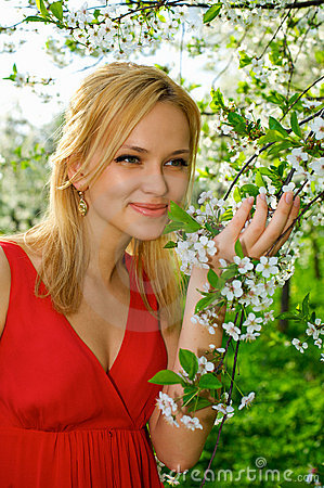 Young woman enjoying smell of blooming tree