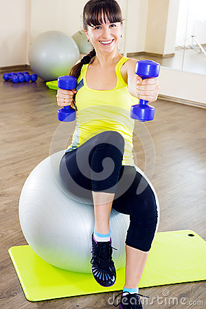 Young woman exercising with dumbbells and fitball