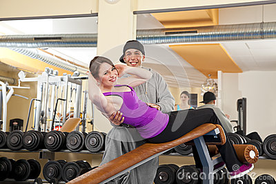 Young woman exercising in gym with trainer