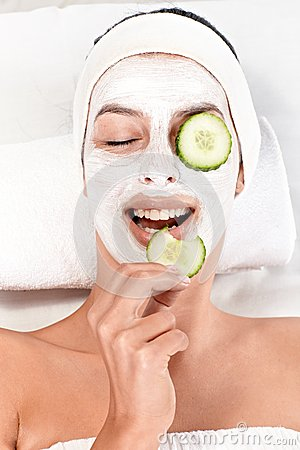 Young woman with face mask and cucumber