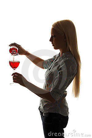 Young woman fills out a glass of red wine