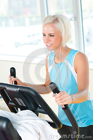 Young woman on fitness machine cardio exercise