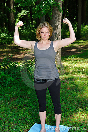 Young woman flexing muscles in park