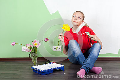 Young woman with flower and paint roller in hands