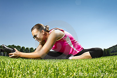 Young woman on the freshly cut grass stretching