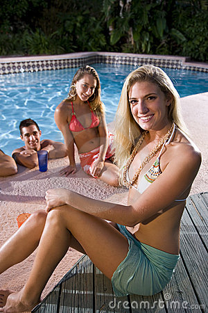 Young woman with friends by swimming pool