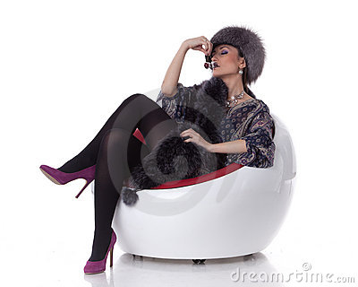 Young woman in fur with cherry sit on armchair.