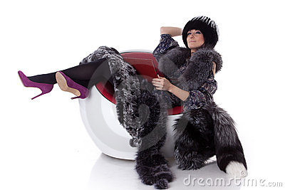 Young woman in fur with laptop sit on armchair