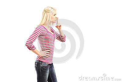 Young woman gesturing silence with finger over mouth