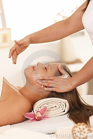 Young woman getting facial massage