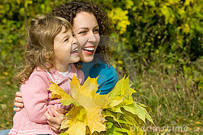 Young woman and girl laugh with leaves in garden