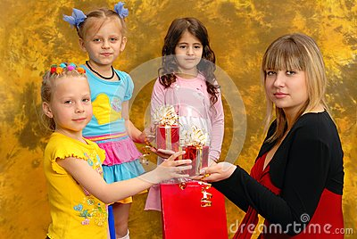 Young woman give gifts to the children