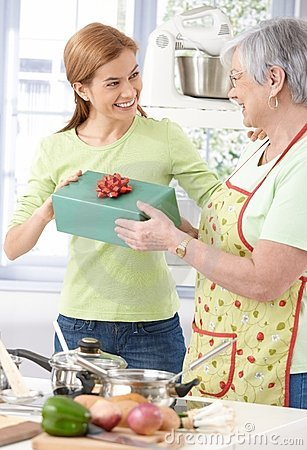 Young woman giving present to mother smiling
