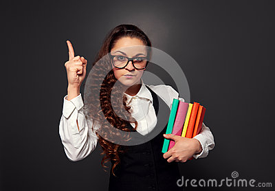 Young woman in glasses with pile of books make attention sign