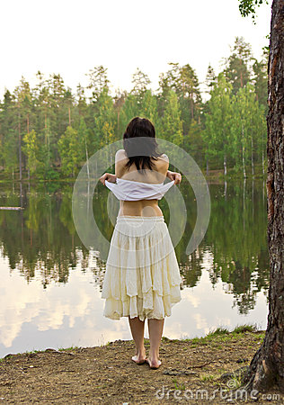 Young woman going to swim in forest lake