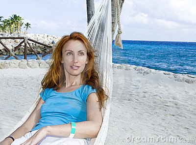 Young woman in hammock on background of palm trees
