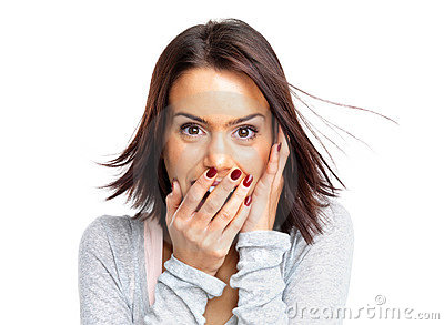 Young woman with hands over her mouth laughing