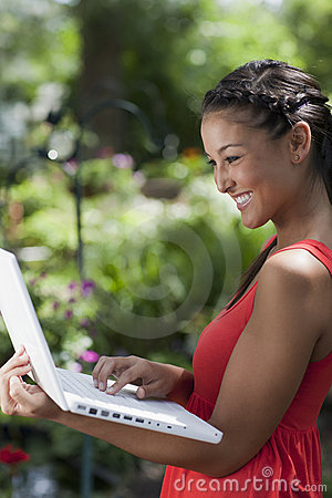 Young Woman Happily Working on a Laptop Outdoors