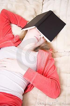 Young woman has fallen asleep reading the book