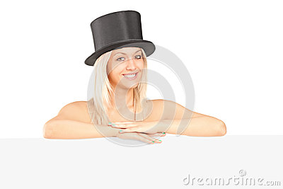 Young woman with a hat posing behind a panel