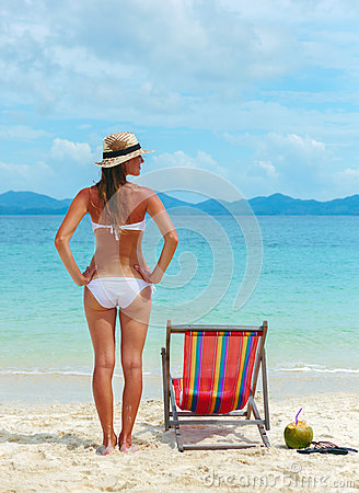 Young woman in hat sunbathing on tropical beach