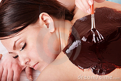 Young woman  having chocolate bodyl mask.