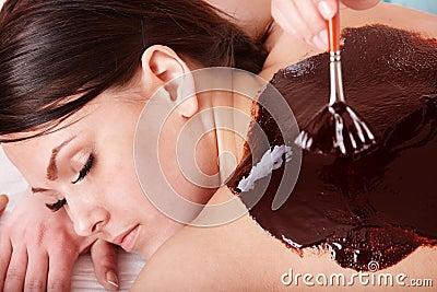 Young woman  having chocolate bodyl mask.