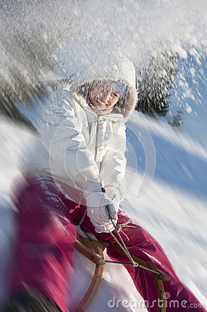 Young woman having fun with sled