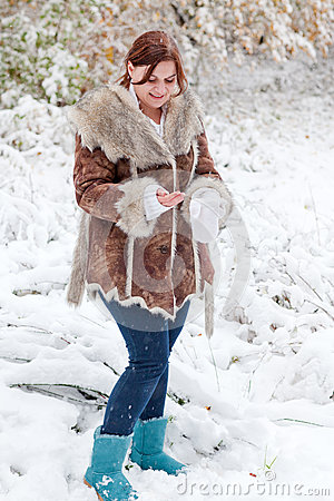 Young woman having fun with snow on winter day