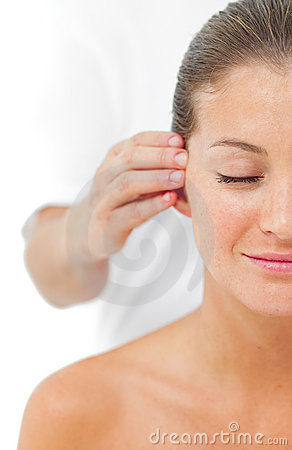 Young woman having a head massage in a spa