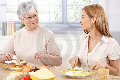 Young woman having lunch with mother smiling