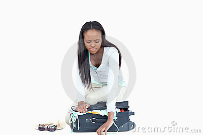 Young woman having problems closing her suitcase