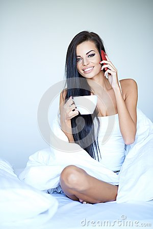 http://thumbs.dreamstime.com/x/young-woman-having-relaxing-day-home-beautiful-sitting-bed-cup-coffee-talking-her-mobile-phone-43916406.jpg