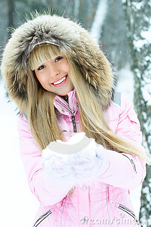 Young woman having a walk in winter forest