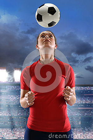 Young Woman Heading Soccer Ball