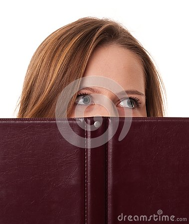 Young woman hides her mouth behind the book