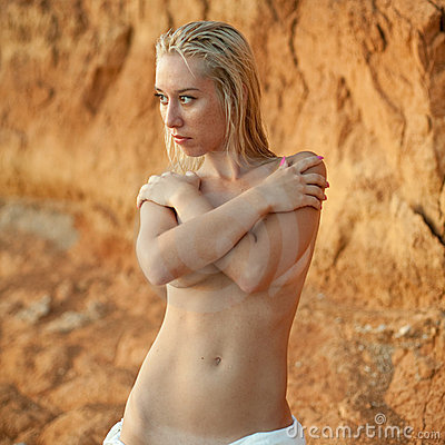 Young woman hides her naked breasts