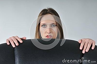 Young woman hiding behind big